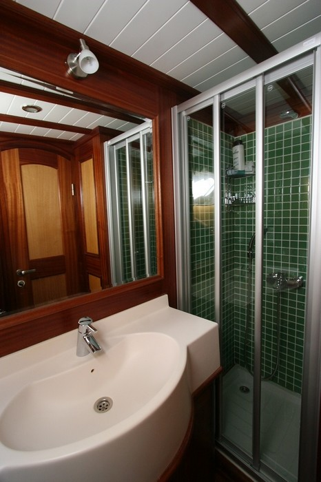 bathroom with green tile in shower